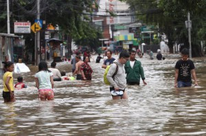 Indonesians wade through flood water on a street in Jakarta, Indonesia, Tuesday, Feb. 25, 2020. Overnight rains caused rivers to burst their banks in greater Jakarta sending muddy water into residential and commercial areas, inundating thousands of homes and paralyzing parts of the city's transport networks, officials said. (AP)