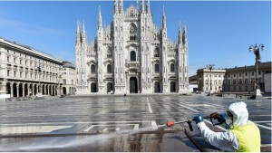A worker wearing protective garments sanitizes the Duomo square, during the coronavirus disease outbreak in central Milan, Italy. (Reuters)