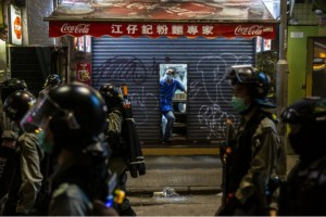 A man (C) leans out from a shop as police conduct a clearance operation in the Causeway Bay district of Hong Kong on May 24, 2020, during protests against a proposal to enact new security legislation in Hong Kong.(AFP)