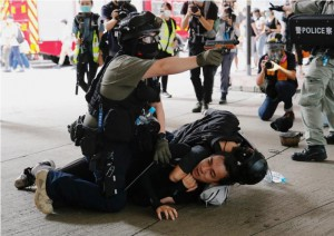 A police officer raises his pepper spray handgun as he detains a man during a march against the national security law at the anniversary of Hong Kong's handover to China from Britain in Hong Kong, China July 1, 2020. (Reuters)