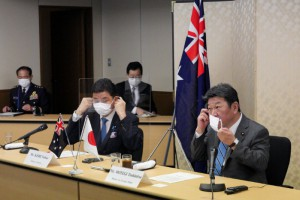 Japanese Foreign Minister Toshimitsu Motegi (R) and Defense Minister Nobuo Kishi remove their protective masks as they attend a video conference with Australian Foreign Minister and Minister for Women Marise Payne and Australian Defense Minister Peter Dutton (not in picture), at Foreign Ministry in Tokyo, Japan June 9, 2021. Eugene Hoshiko/Pool via REUTERS